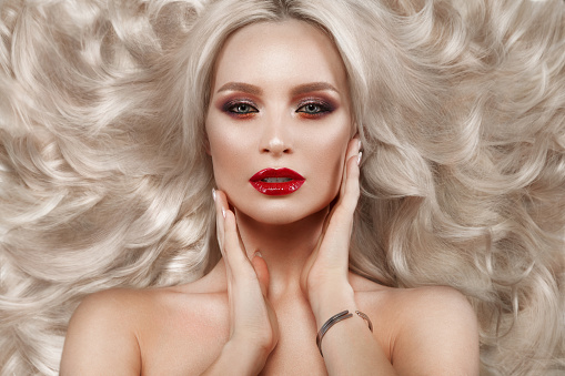 istock Beautiful blonde in a Hollywood manner with curls, natural makeup and red lips. Beauty face and hair. 940362578
