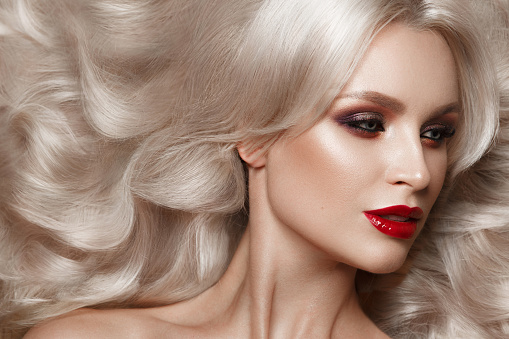 istock Beautiful blonde in a Hollywood manner with curls, natural makeup and red lips. Beauty face and hair. 940362582