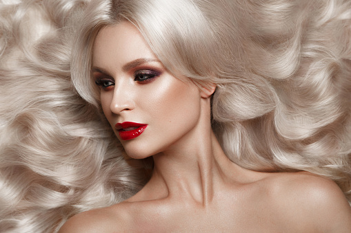 istock Beautiful blonde in a Hollywood manner with curls, natural makeup and red lips. Beauty face and hair. 940362584