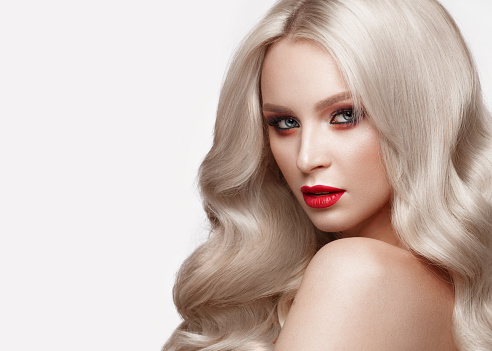 istock Beautiful blonde in a Hollywood manner with curls, natural makeup and red lips. Beauty face and hair. 940362594