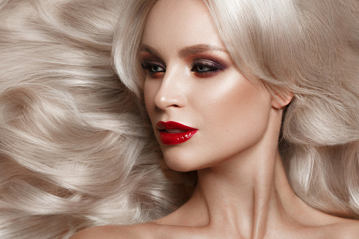 istock Beautiful blonde in a Hollywood manner with curls, natural makeup and red lips. Beauty face and hair. 940362596