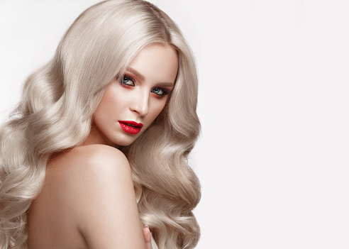 istock Beautiful blonde in a Hollywood manner with curls, natural makeup and red lips. Beauty face and hair. 940362604