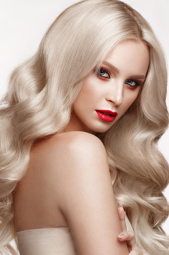 istock Beautiful blonde in a Hollywood manner with curls, natural makeup and red lips. Beauty face and hair. 940362606