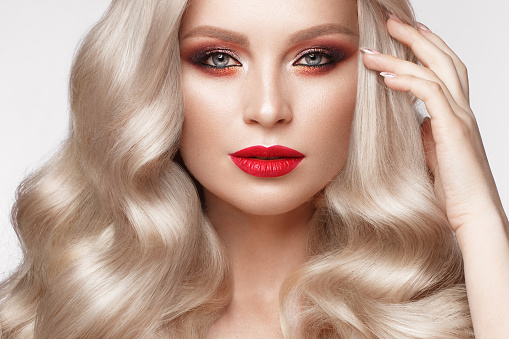 istock Beautiful blonde in a Hollywood manner with curls, natural makeup and red lips. Beauty face and hair. 940362610