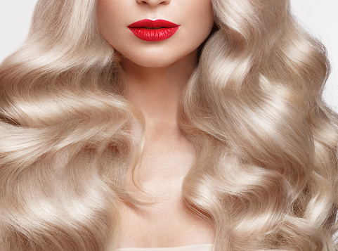 istock Beautiful blonde in a Hollywood manner with curls, natural makeup and red lips. Beauty face and hair. 940362614