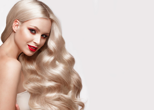 istock Beautiful blonde in a Hollywood manner with curls, natural makeup and red lips. Beauty face and hair. 940362634