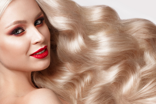 istock Beautiful blonde in a Hollywood manner with curls, natural makeup and red lips. Beauty face and hair. 940362638