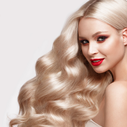 istock Beautiful blonde in a Hollywood manner with curls, natural makeup and red lips. Beauty face and hair. 940362640