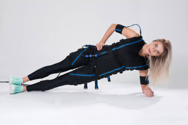 Beautiful blonde in an electric muscular suit for stimulation makes an exercise on the rug stock photo