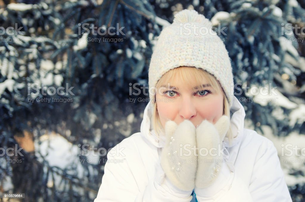 A beautiful blonde in sports clothes warms her chin with warm mittens in the forest against the background of snow-covered fir tree stock photo