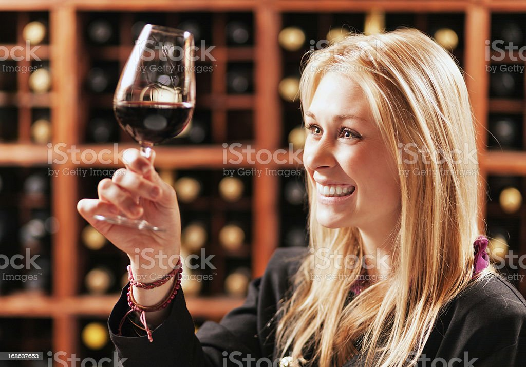 Beautiful blonde in winery cellar toasts with red wine royalty-free stock photo