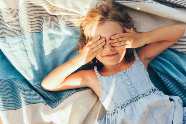 Beautiful blonde little girl lying on the blanket, cover her eyes from the sun with both hands, enjoying summer day. Adorable child having fun and plaiyng peekaboo outdoors in the park stock photo