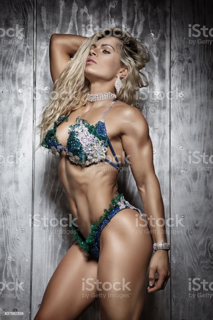 Beautiful blonde muscled female fitness model posing for studio pics stock photo