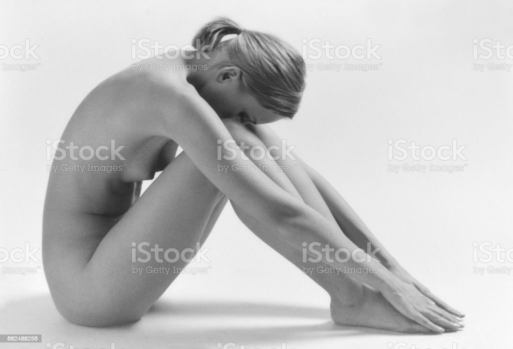 Beautiful blonde nude woman sitting on white background. Black & white film scan. Film grain. royalty-free stock photo