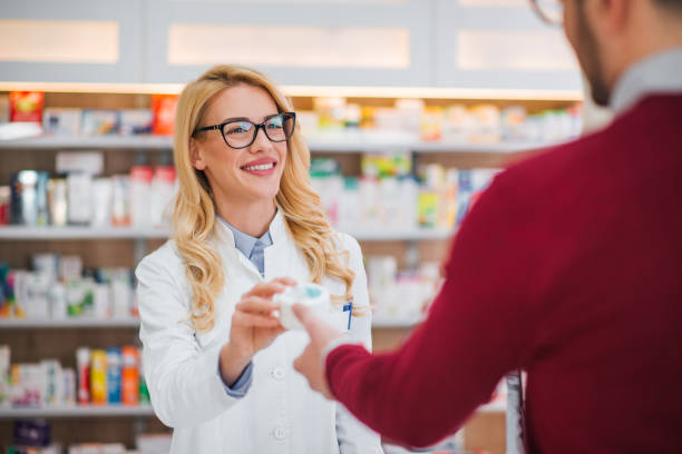 Beautiful blonde pharmacist giving medicament to a patient. Beautiful blonde pharmacist giving medicament to a patient. pharmacist stock pictures, royalty-free photos & images
