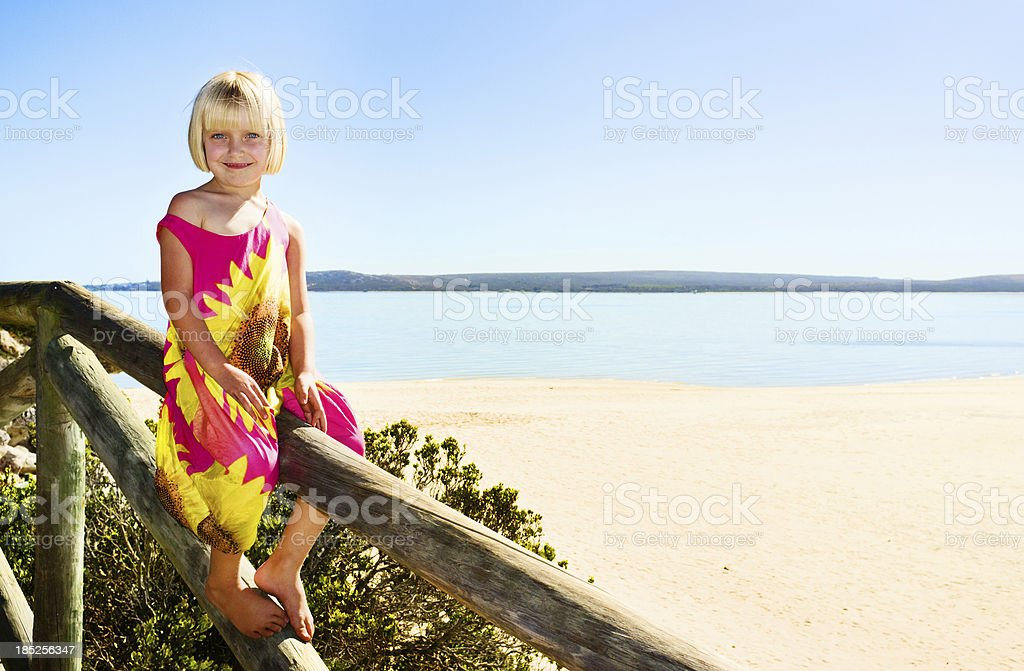 Beautiful blonde pre-schooler on beachside walkway with sea in background stock photo