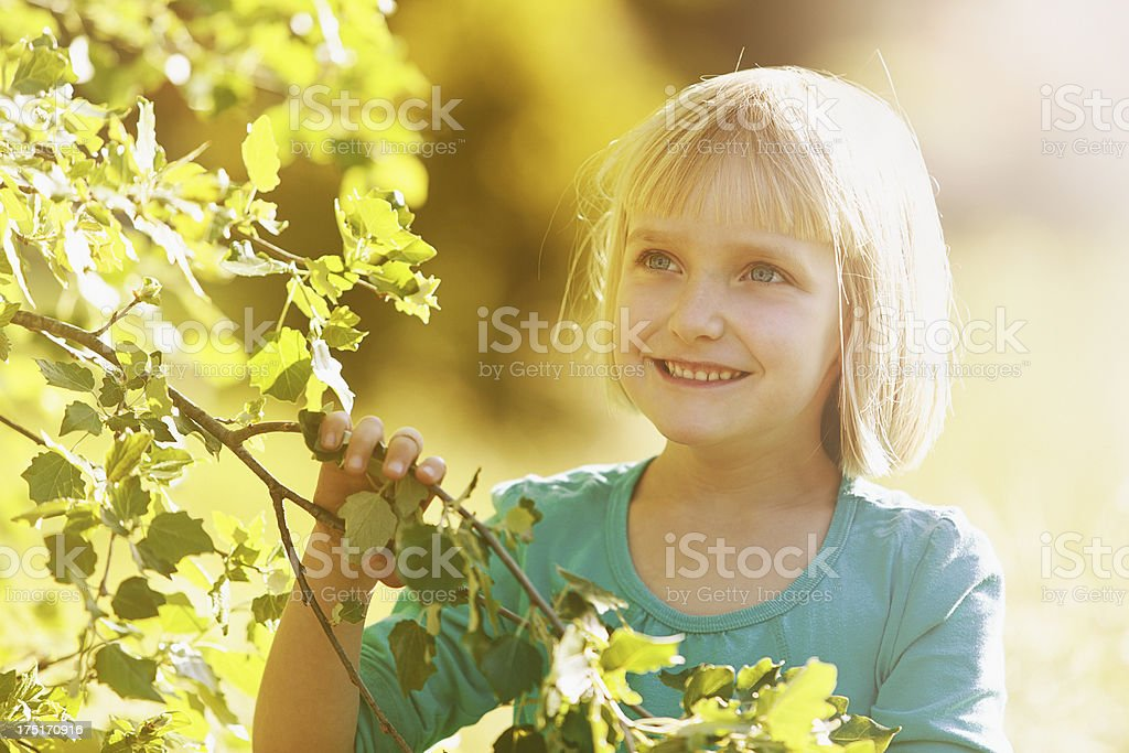 Beautiful blonde pre-schooler smiling in spring sunshine next to tree stock photo