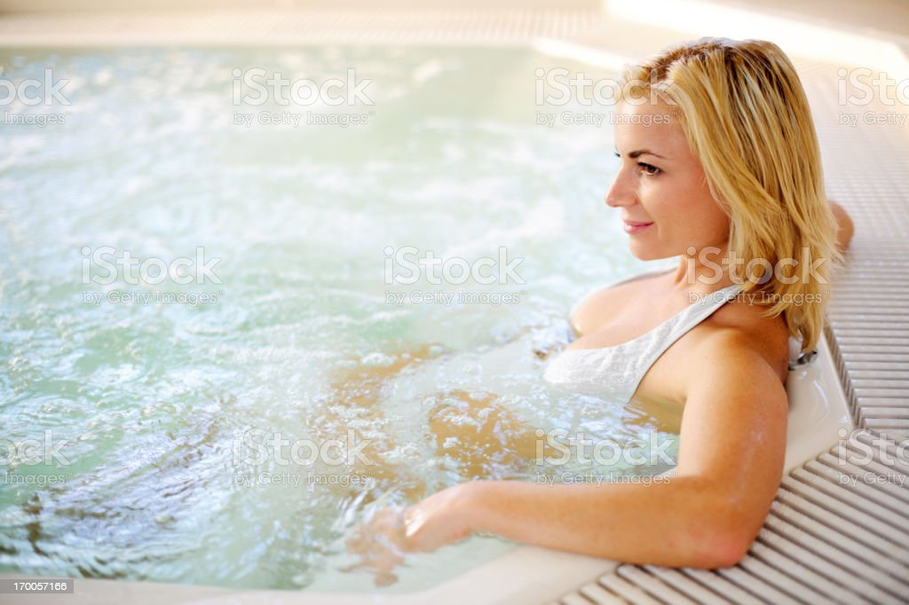 Beautiful blonde relaxing herself in the Jacuzzi. royalty-free stock photo