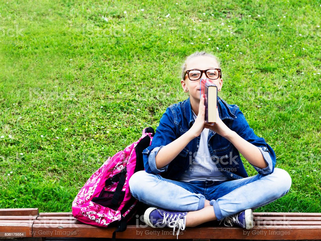Beautiful blonde schoolgirl girl in jeans shirt reading a book on grass with a backpack in the park Education. stock photo