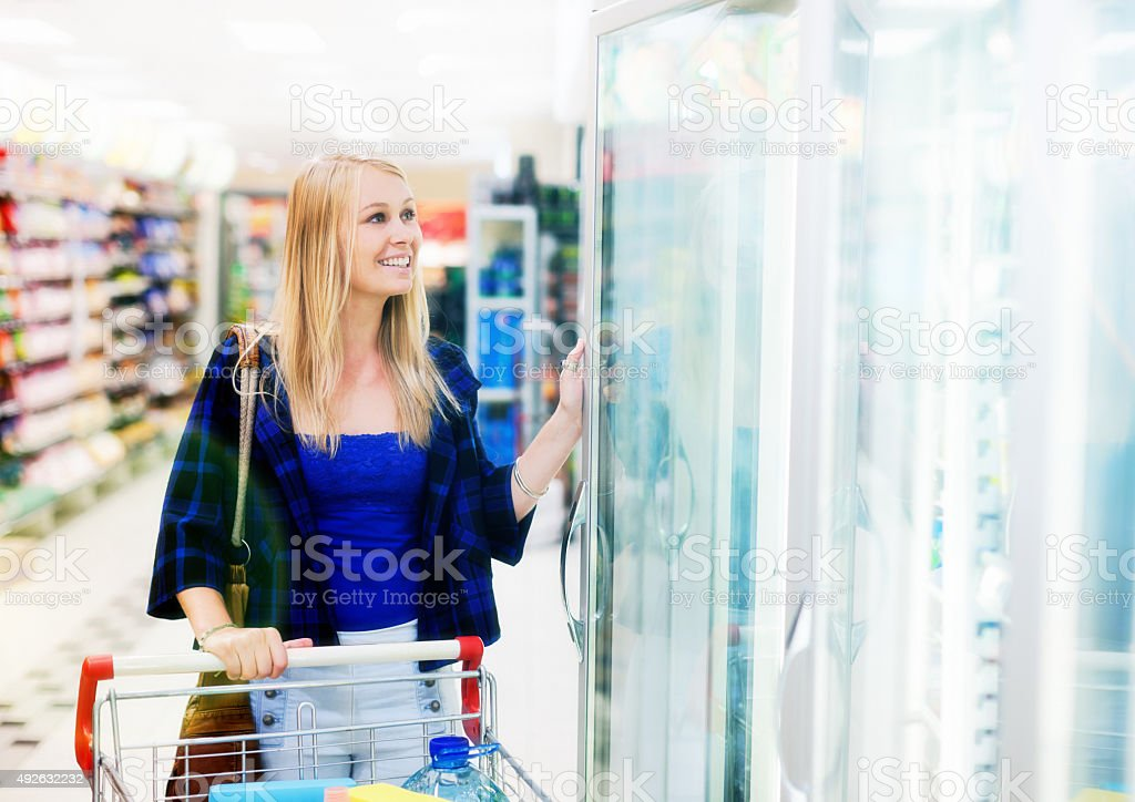 Beautiful blonde shopper by supermarket refrigerator smiles stock photo