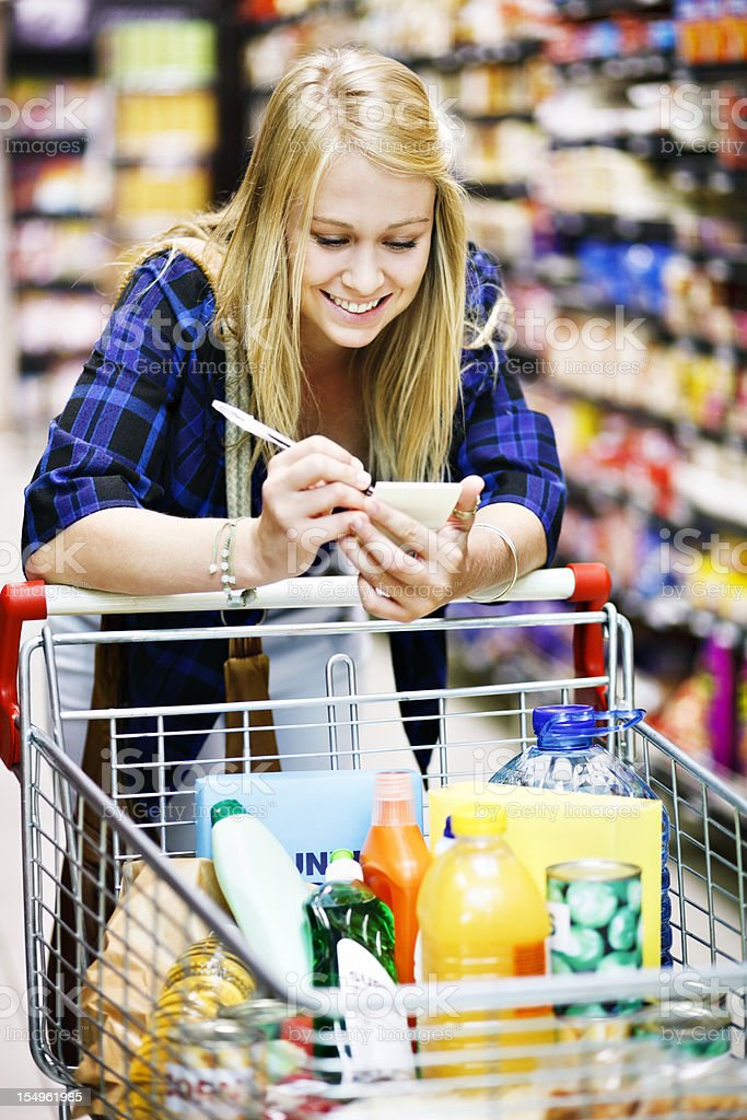 Beautiful blonde shopper in supermarket checks her shopping list stock photo