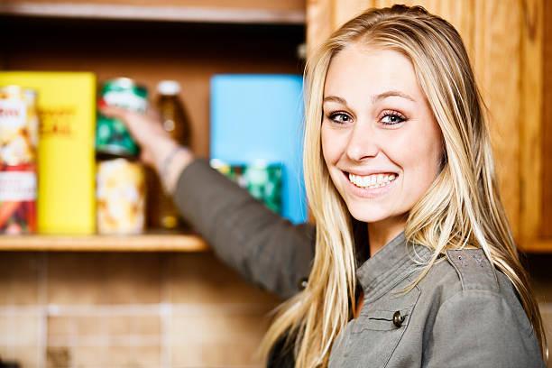 beautiful blonde smiles as she reaches into grocery cupboard - looking inside inside cabinet bildbanksfoton och bilder