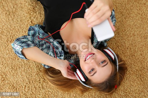 istock Beautiful blonde smiling woman lying on carpet floor wearing hea 520611482