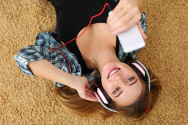 hermosa rubia sonriente mujer tendido sobre piso alfombrado usa hea - auriculares equipo de música fotografías e imágenes de stock