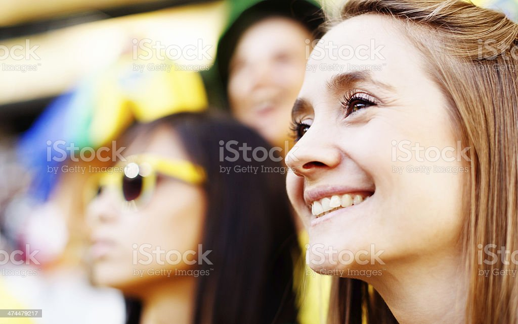 Beautiful blonde soccer fan and friend smiling at football match stock photo