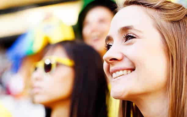wunderschöne blonde fußball-fan und freund lächelnd im fußball - spielerfrauen stock-fotos und bilder