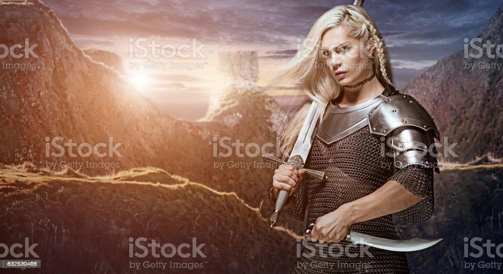 Beautiful Blonde Sword wielding viking warrior female stock photo