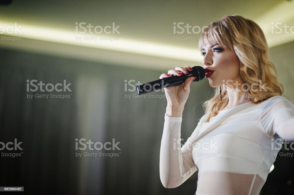 Beautiful blonde vocal singer girl on stage. stock photo