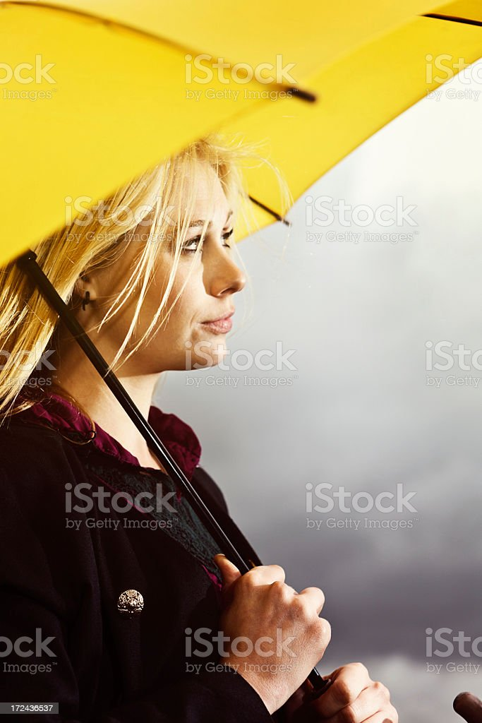 Beautiful blonde waits patiently under umbrella for storm to pass royalty-free stock photo