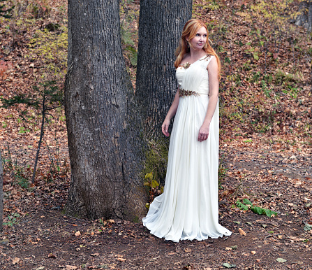 Beautiful blonde wearing white dress of princess in the forest
