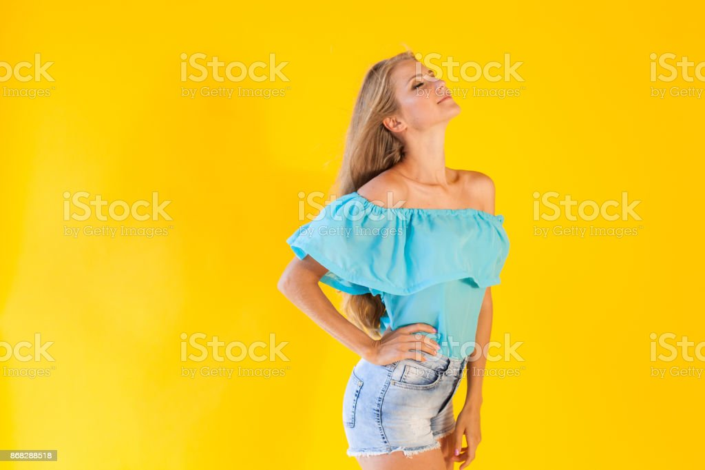beautiful blonde with blue shorts on a yellow background stock photo