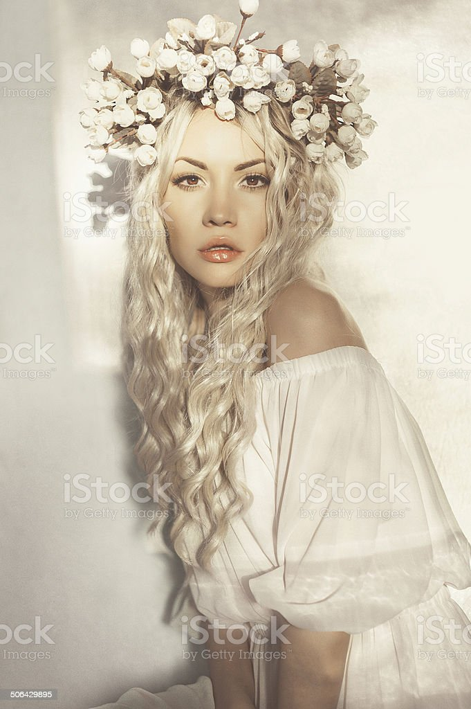 Beautiful blonde with wreath of flowers stock photo