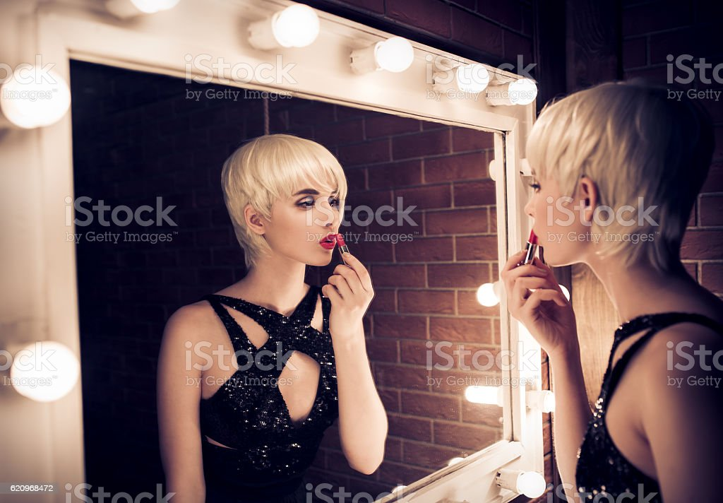 Beautiful Blonde Woman Apply Lipstick Looking Into Mirror stock photo