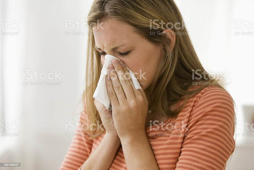 Beautiful caucasian young woman blowing her nose at home, horizontal...