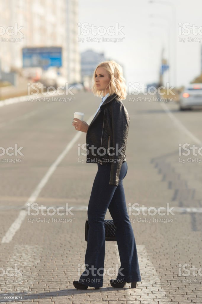 Beautiful blonde woman cross the road with a take away coffee. Street fashion look. stock photo