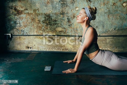 Self care rituals:  woman wearing wireless earphones using her mobile phone during her yoga practice.