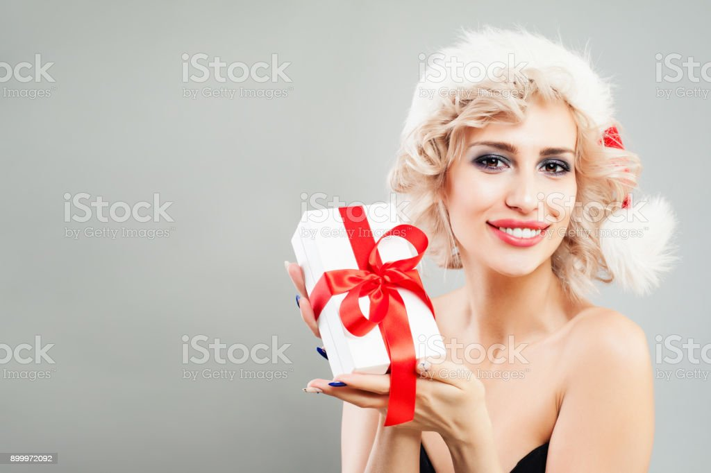 095c7254cfefd Beautiful Blonde Woman Fashion Model holding Christmas Gift on Grey Banner  Background with Copy space. Perfect Woman in Santa Hat - Stock image .