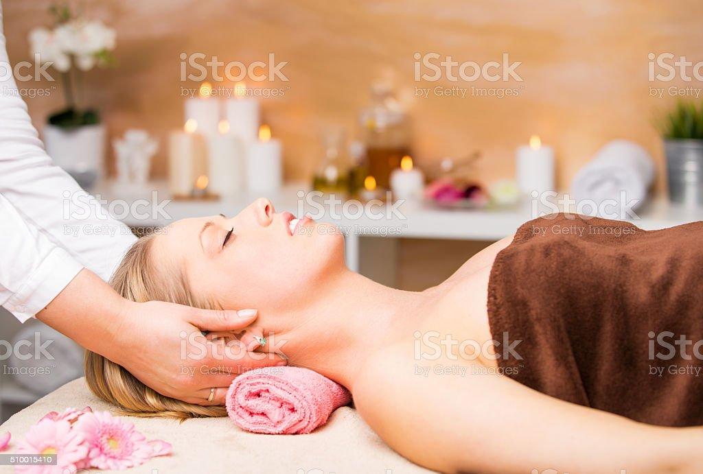 Beautiful blonde woman getting facial massage at spa stock photo