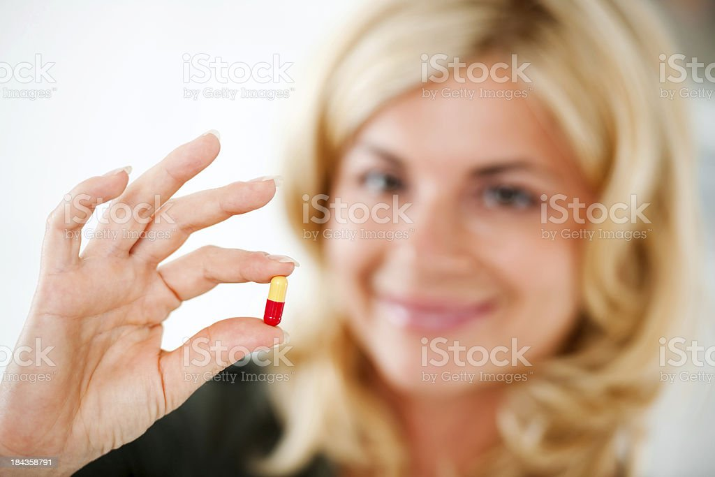 Beautiful blonde woman holding a pill. royalty-free stock photo