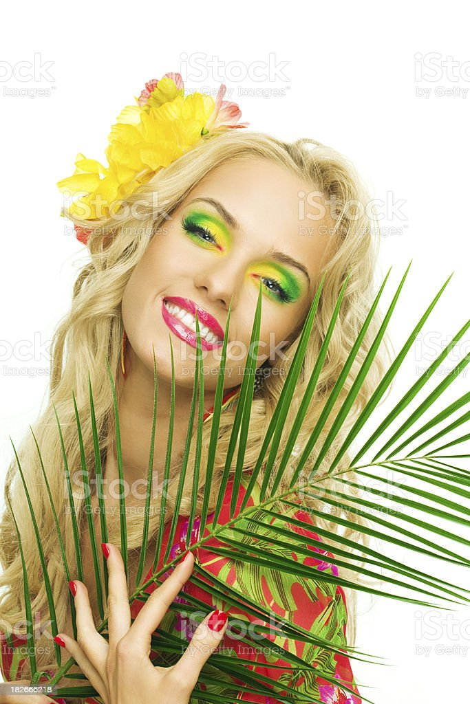 Beautiful blonde woman holding large tropical leaf. Summer portrait of a beautiful blonde woman wearing a colorful tunic. Holding large tropical leaf. 20-24 Years Stock Photo