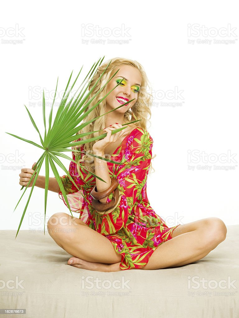 "Beautiful blonde woman holding large tropical leaf. ""Summer portrait of a beautiful blonde woman sitting with her legs crossed,wearing a colorful tunic. Holding large tropical leaf."" 20-24 Years Stock Photo"