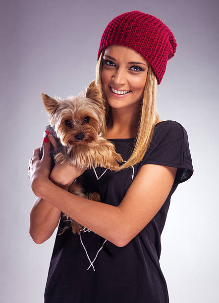 Beautiful blonde woman in autumn dress, holding  yorkshire terrier stock photo