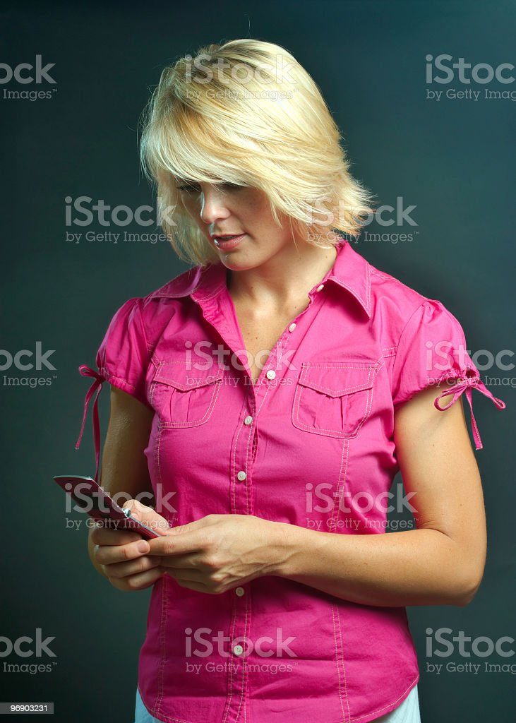 Beautiful blonde woman in pink looking at cell phone royalty-free stock photo