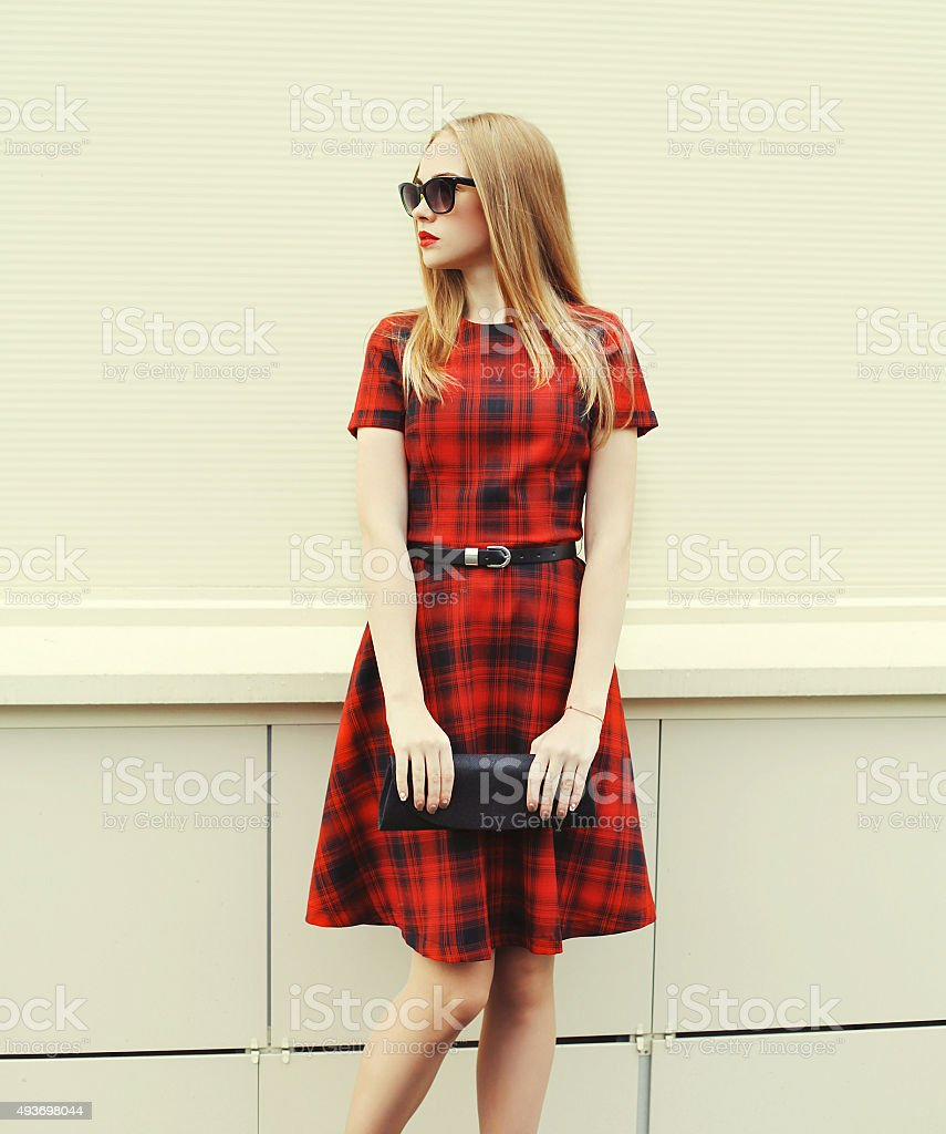 Beautiful blonde woman in red dress, sunglasses with handbag clu stock photo