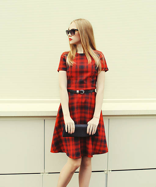 Beautiful blonde woman in red dress, sunglasses with handbag clu Beautiful blonde woman in red dress, sunglasses with handbag clutch, profile view plaid stock pictures, royalty-free photos & images