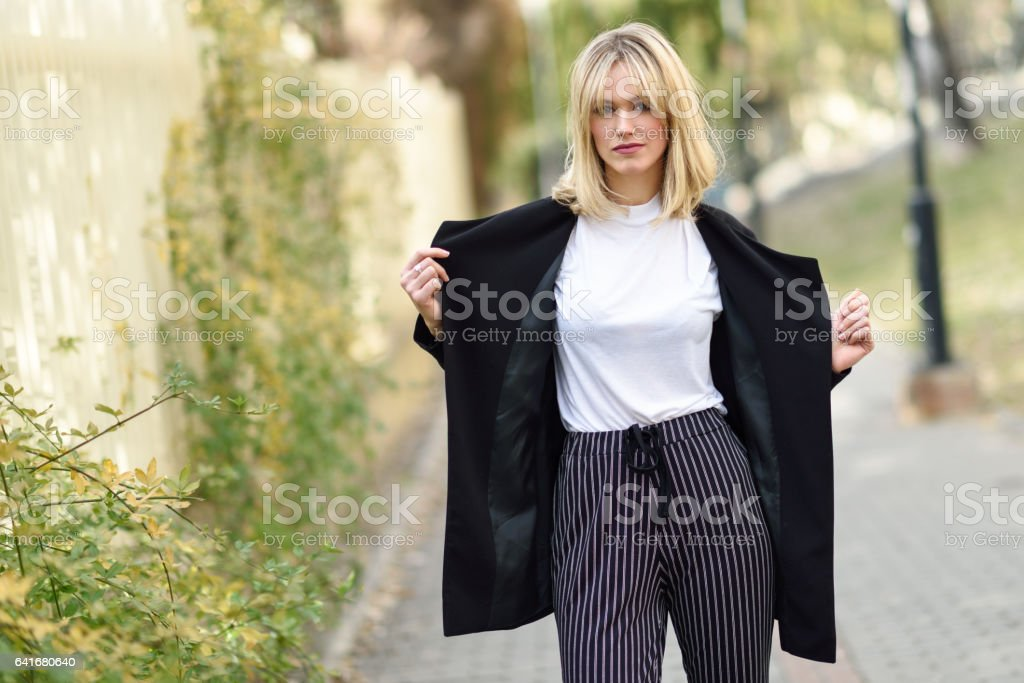 Beautiful blonde woman in urban background. stock photo
